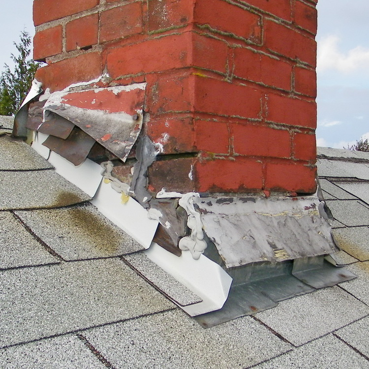 Cracked Chimney Flashing which can be seen during a roof inspection